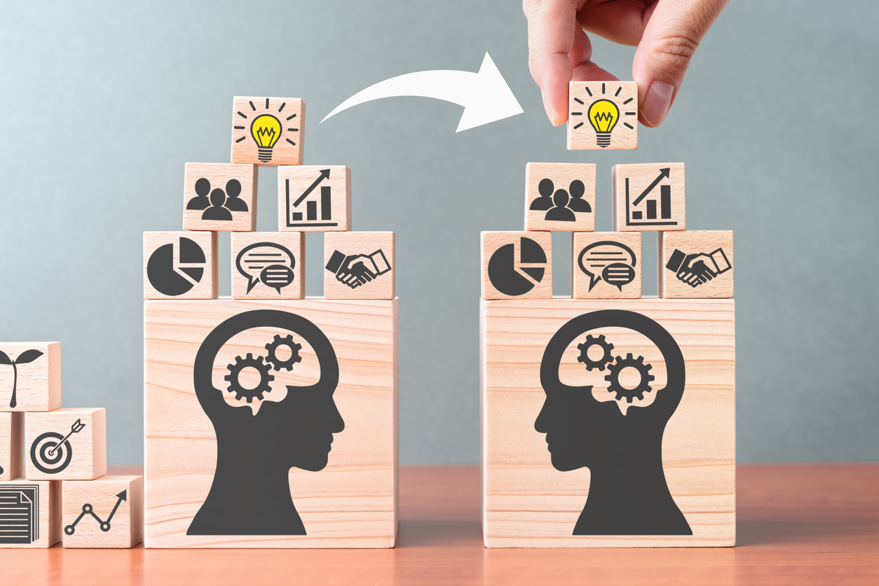 A concept of business coaching, blocks showing a person transferring ideas and knowledge from one person to another.