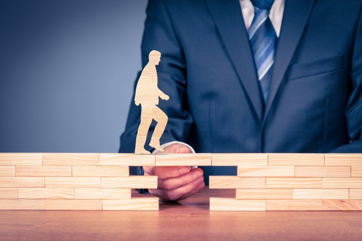 Businessman's hand holding wooden blocks showing business growth and continuity.