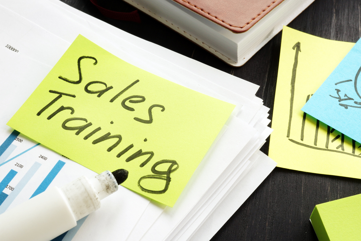 Sales training program concept, a note with the words sales training placed on a table together with other company data and graphs.