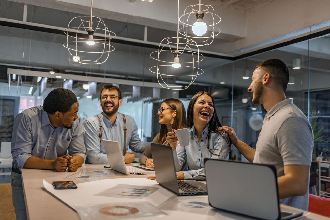 Team of diverse employees having fun in the workplace while getting their job done.