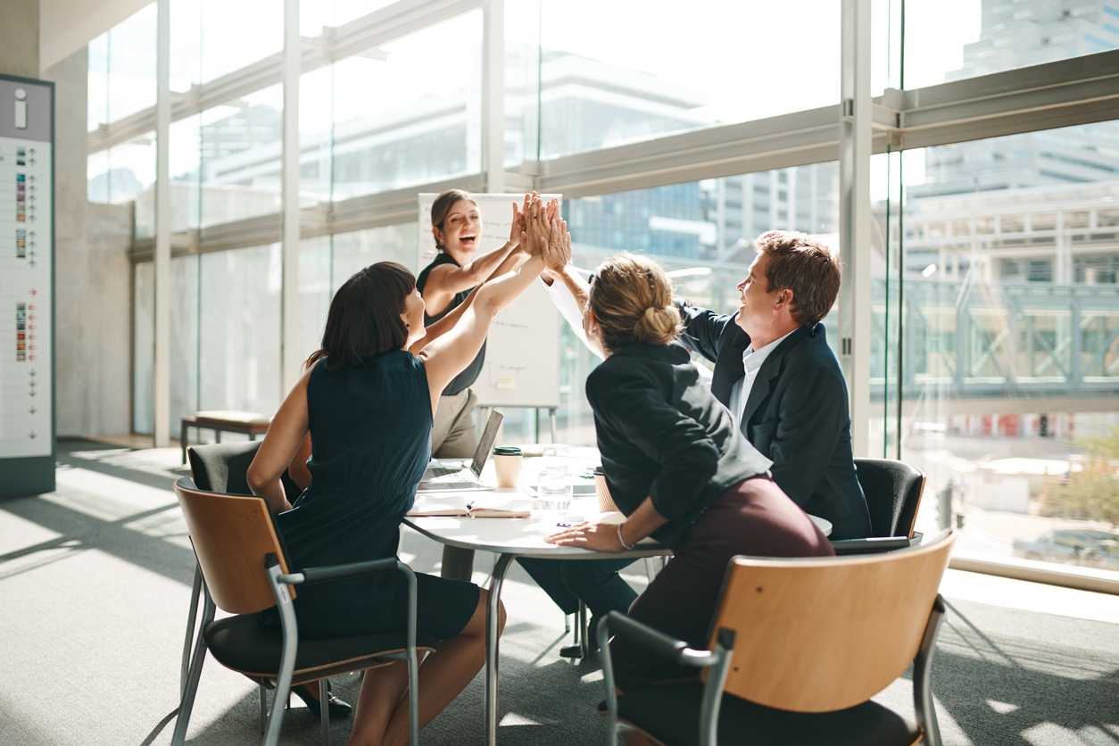 Team of diverse employees in an office high-fiving each other as a sign of agreement with their business ideas.