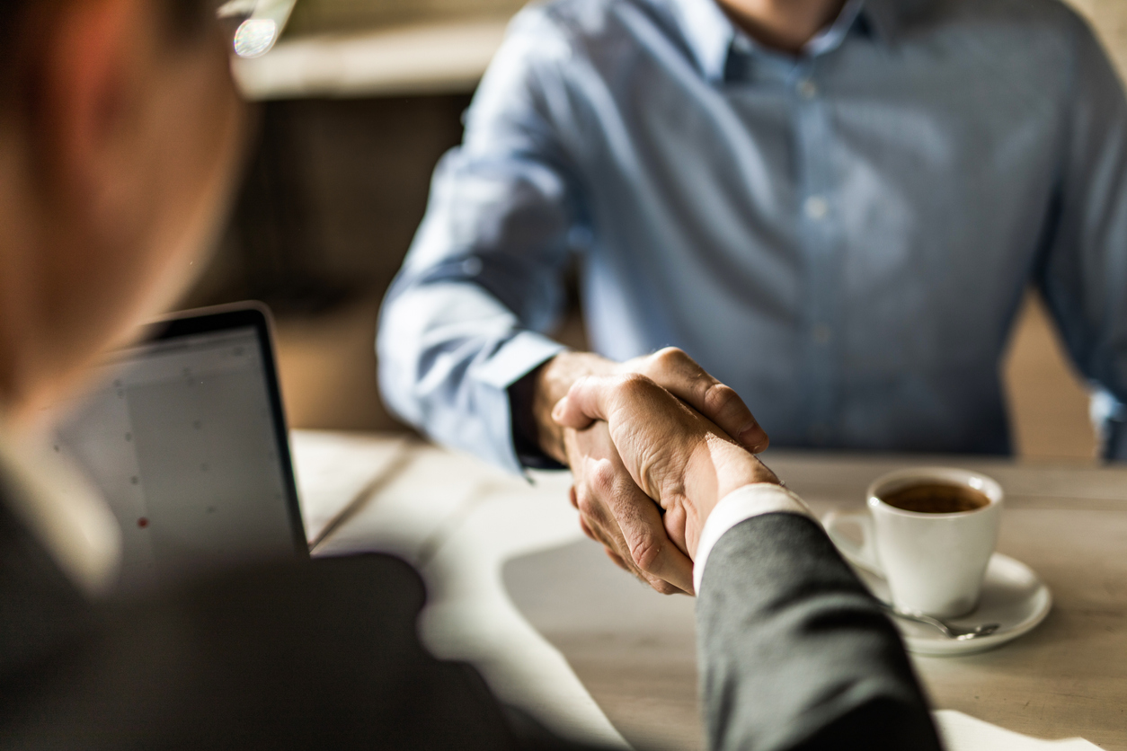 Businessman shaking hands with a male client during a business meeting in a cafe.