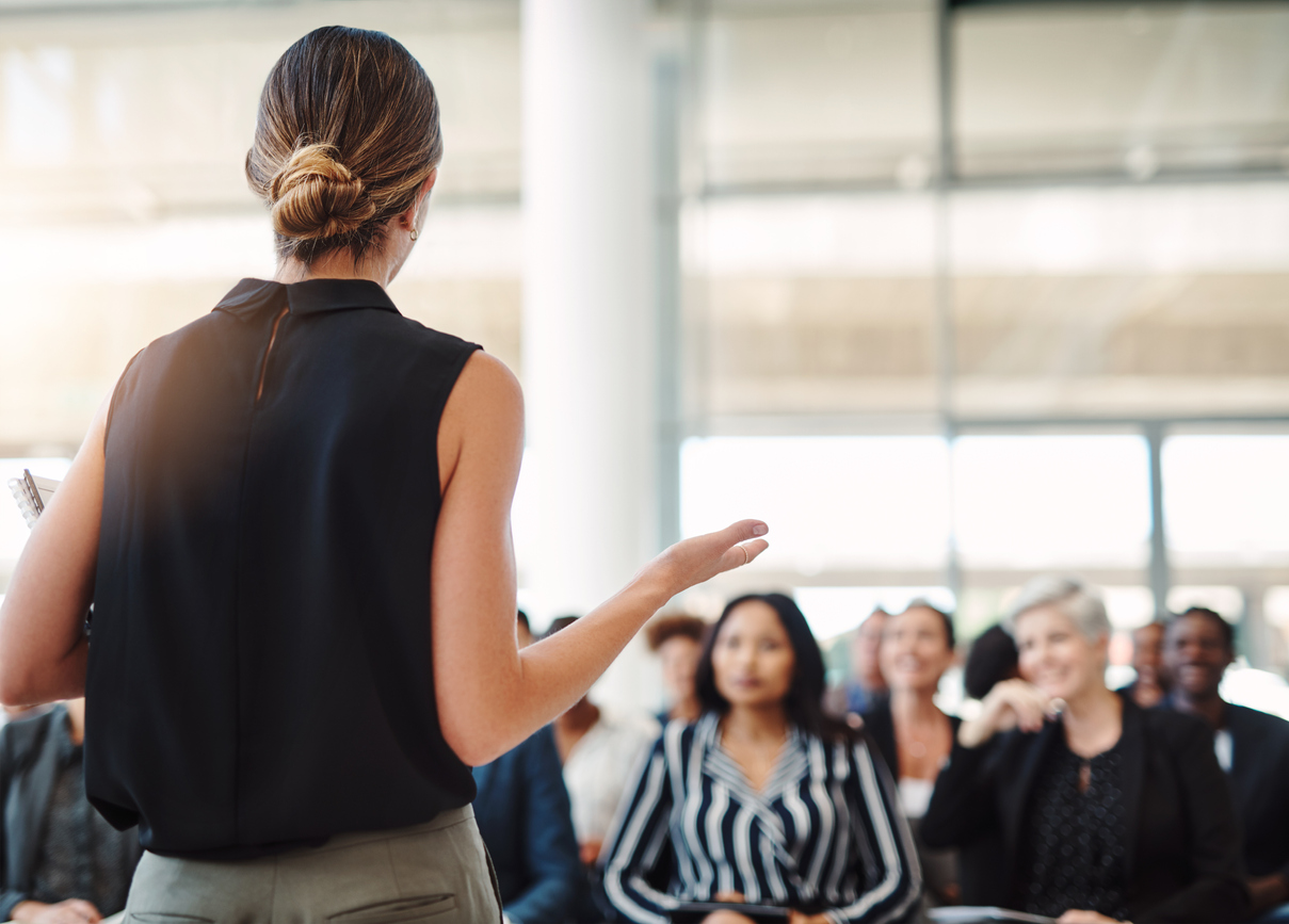Female entrepreneur giving a lecture to a group of people in a conference room.