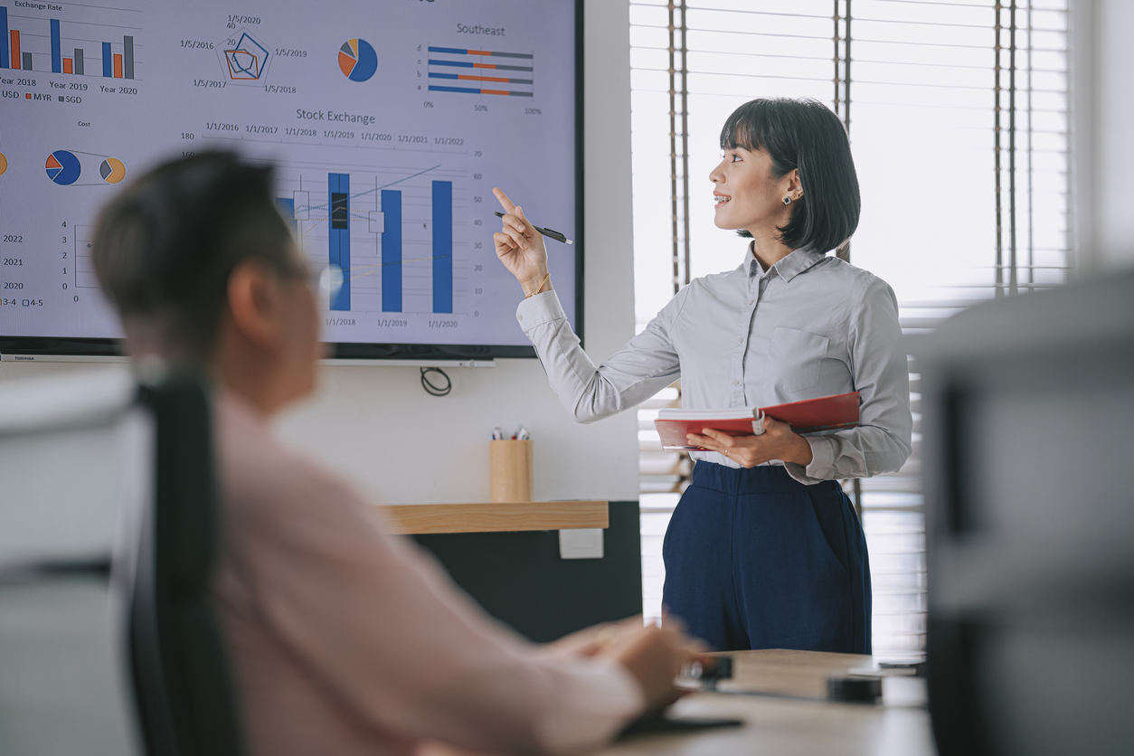 Female coach giving a training program to a group of sales people in an office.