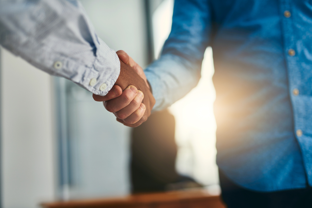 Businessman and prospective customer shaking hands in an office showing a concept of agreement regarding B2B deals.