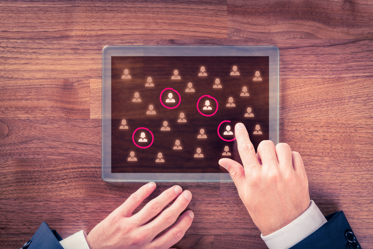 Businessman's hands encircling their company's target customers shown on a tablet device.