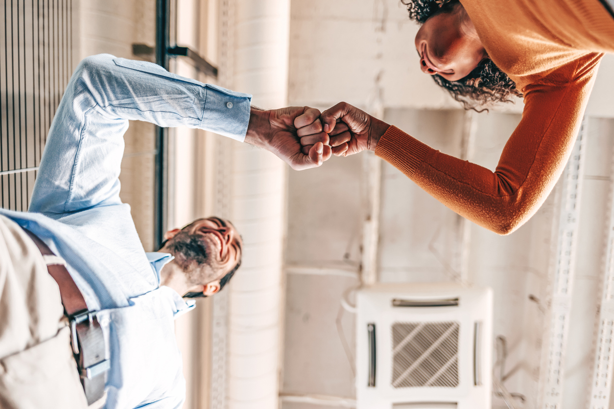 Two salespeople in an office fist bumping each other, celebrating accomplishments with their company's sales.