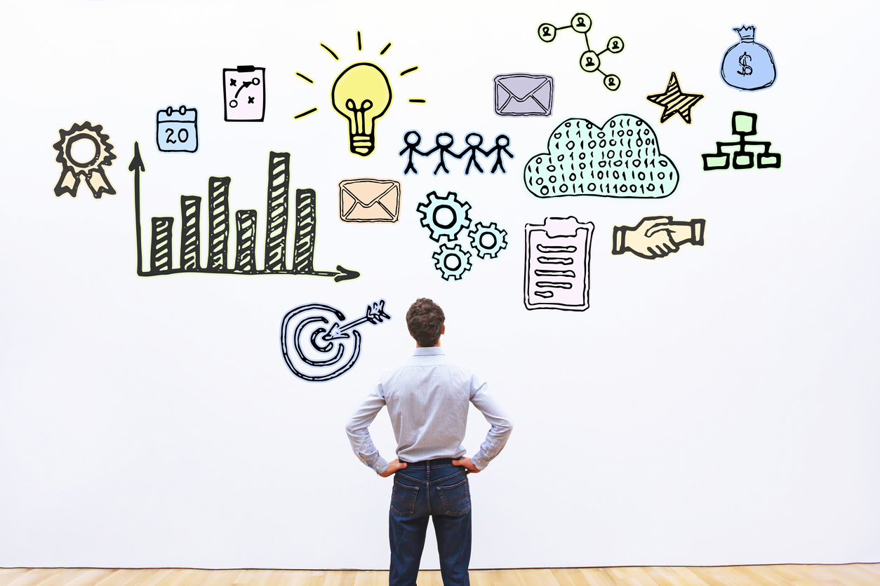 Businessman looking at an illustration of different business concepts.