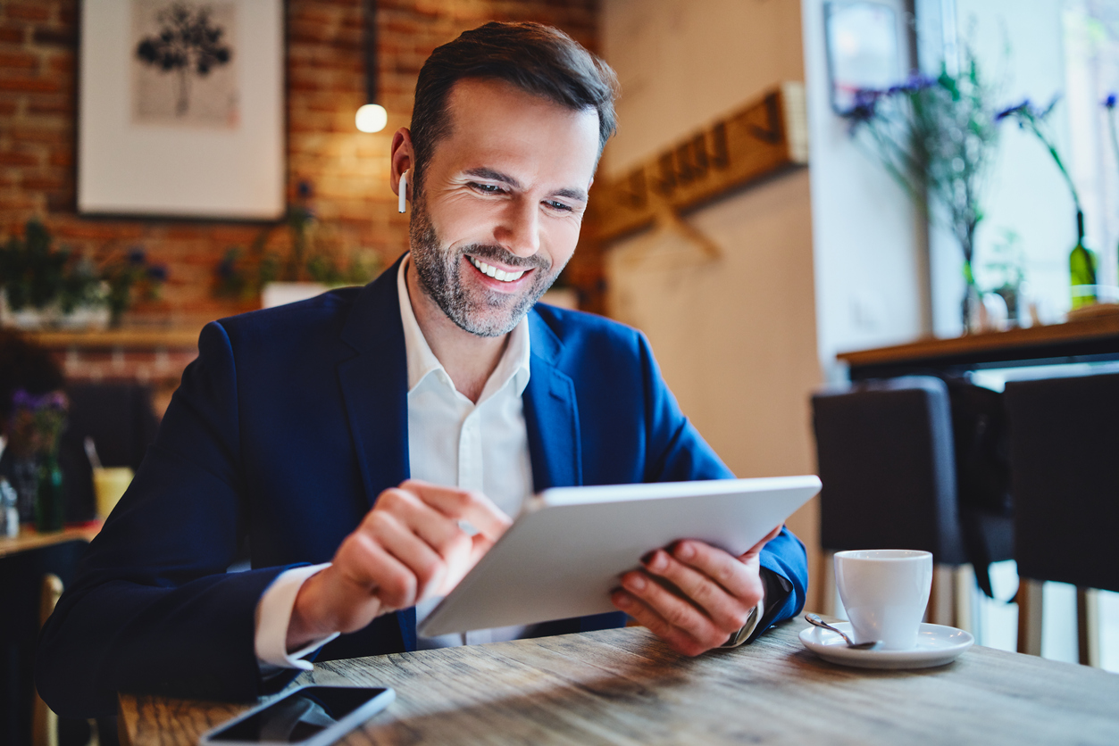Businessman using a tablet device to reach out to his prospects and manage their business needs.