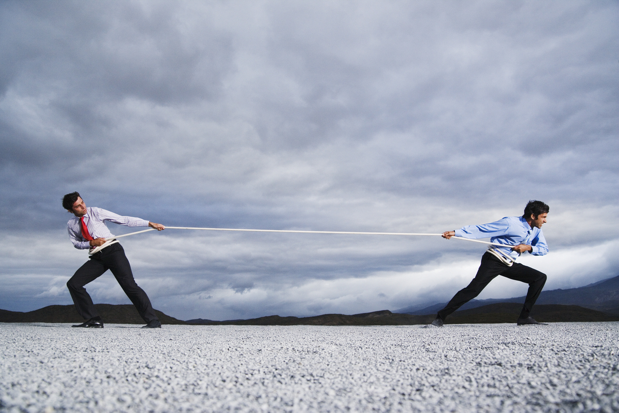 A concept of winning against your competitors - businessmen playing a game of tug of war.